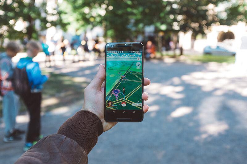 Handy in der Hand und PokemonGo auf dem Bildschirm.